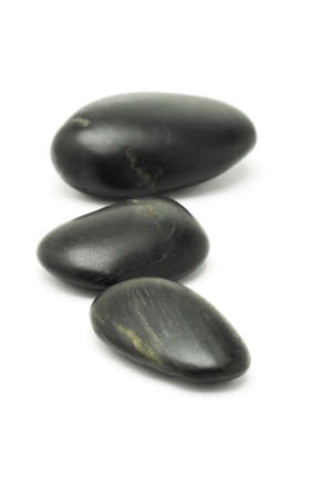 three color: Three pieces of black pebble stone on white background