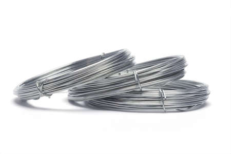 Coils of galvanized wires lying on white background