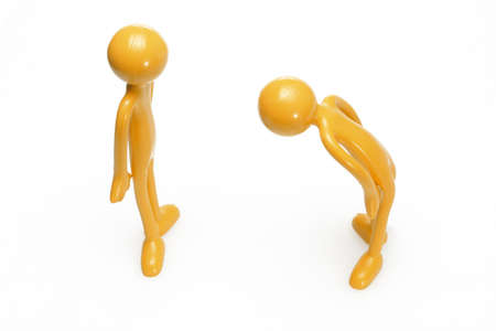 bowing: Toy rubber figurine bowing to another on white background Stock Photo