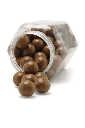 Chocolate balls spilling out from fallen plastic container  photo