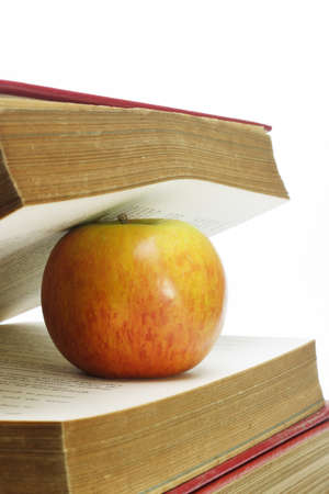 between: Close up of apple and old books on white background Stock Photo