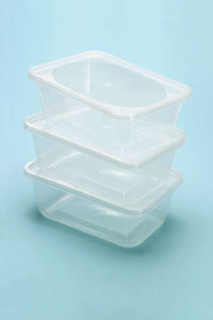 plastic box: Stack of empty transparent plastic boxes on blue background