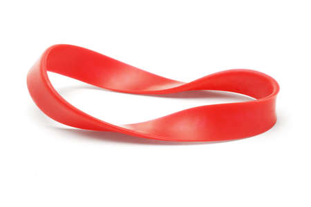Twisted red rubber wrist band on white background photo