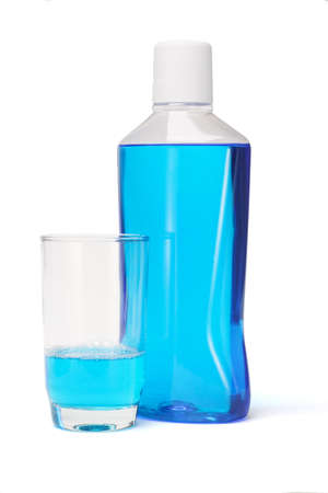 Plastic bottle and glass of mouthwash on white background photo