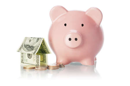 Savings and investment - Piggy bank, money house and coins on white background photo
