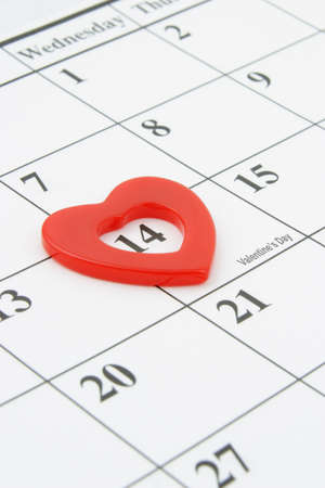 Heart shape marker on calendar page showing February 14 Valentines Day photo