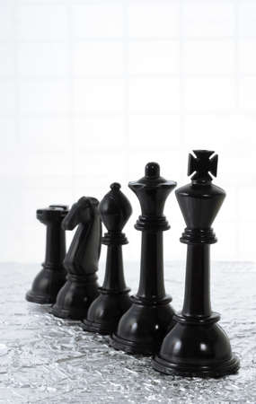 Row of black chess pieces on creased silver metallic sheet and grid background photo