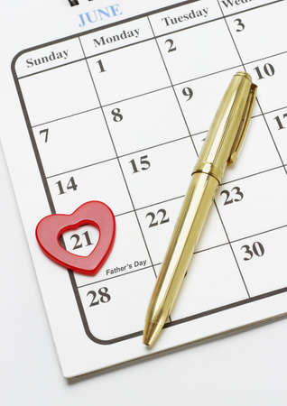 Heart shape symbol and gold fountain pen on calendar page showing date of Fathers day photo