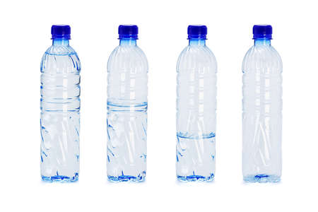 Different water levels in plastic bottles on white background photo