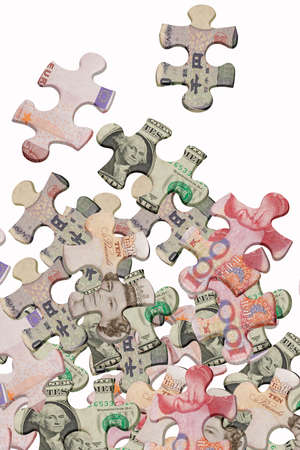 mismatch: Jigsaw puzzles superimposed with world major currencies scattered on white background