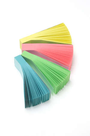 stacks of colorful narrow sticky packs on white background photo