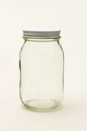 Empty glass jar on seamless color background photo