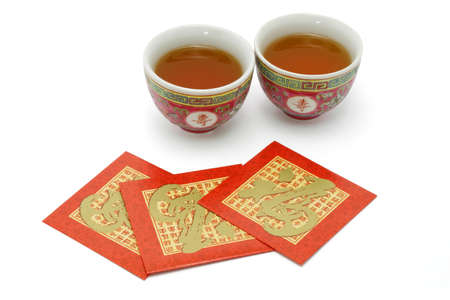 Chinese longevity tea cups and red packets for tea ceremony on white background photo