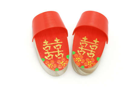 Pair of hand painted red Double Happiness clogs on white background photo