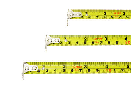 Measuring tapes of different lengths extended horizontally on white background with copy space photo