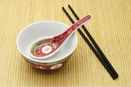 Chinese traditional bowl, spoon and chopsticks arranged on bamboo mat Stock Photo - 10388448
