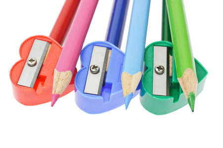 Color pencils and sharpeners arranged on white background photo