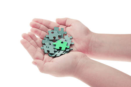Pieces of jigsaw puzzle in boys hands and one is highlighted photo