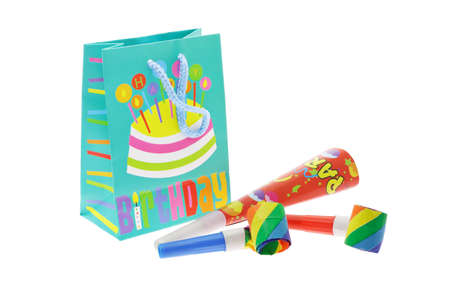 novelties: Colorful gift bag and party blowers on white background Stock Photo