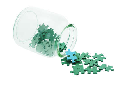Blue piece among all green jigsaw puzzles spilled from glass bottle Stock Photo - 10396819