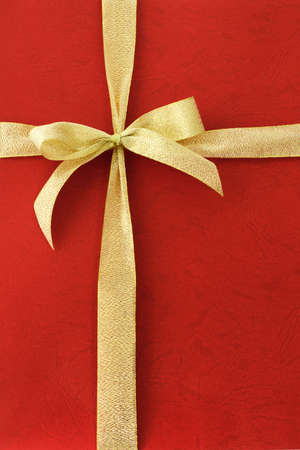 gold top: Gold color bow ribbon on red background Stock Photo