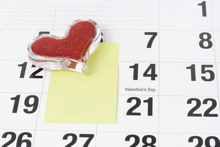 Heart shape glass paper weight and note paper on calendar page showing Febraury 14 Valentine's Day Stock Photo - 10457626