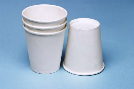 Stack of disposable paper cups on blue background photo