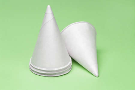 Cone shape disposable paper cups on green background photo