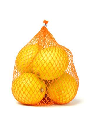 netting: Verse citroenen in plastic netten zak op een witte achtergrond