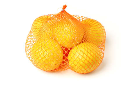 Fresh lemons in plastic netting sack on white background