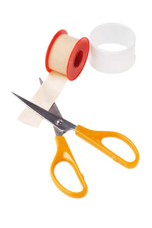 Roll of Medical Sticking Plaster and Pair of Cutting Scissors on White Background photo