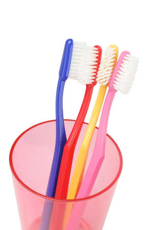 fluoride: Colorful Toothbrushes In Plastic Container On White Background Stock Photo
