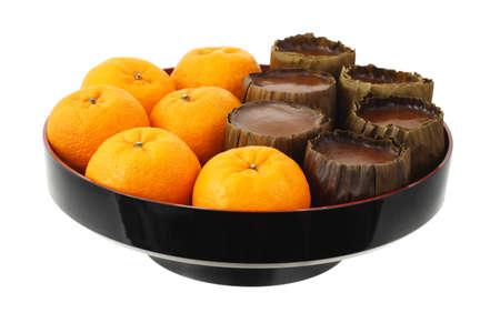 mandarin oranges: Chinese New Year Mandarin Oranges and Rice Cakes On White Background