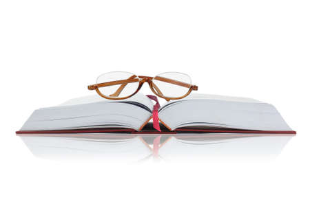 hardcover book: Reading Glasses on an Open Hardcover Book With Copy Space Stock Photo