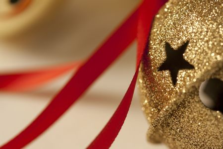 Christmas sleigh bell ornament with red ribbon.