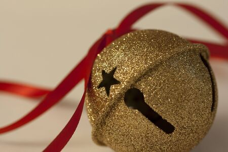 Macro view of a golden sleigh bell Christmas ornament tied with red ribbon. Stock Photo
