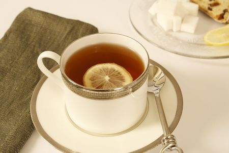 White porcelain cup of hot tea with lemon slice. Stock Photo