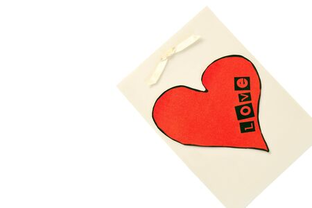 Cut out red heart on vellum with a white ribbon for Valentines Day. Stock Photo