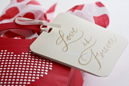 Valentines Day gift with silver studded heart on a red bag with a gift tag. Stock Photo