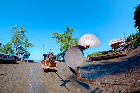 folkways: small fishing boat on the ground after ebb tide Stock Photo