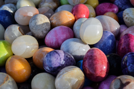 Colourfull eggs made of stone placed as a textured background.