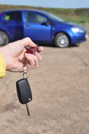 automatically: automatically unlock the doors, the hand that directs them to the machine, which stands in the background, yellow sleeves and a sign on the protection of the vehicle Stock Photo