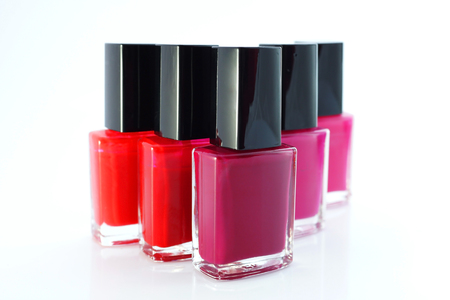 spilled paint: Group of red nail polishes on white