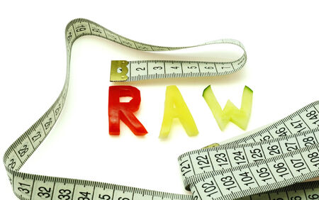 Word raw composed of slices of different vegetables with measuring tape on white  background photo