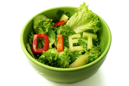 starvation: Green plate with word diet composed of slices of different vegetables on salad