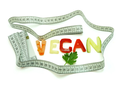 Word vegan composed of slices of different vegetables with measuring tape on white  background photo
