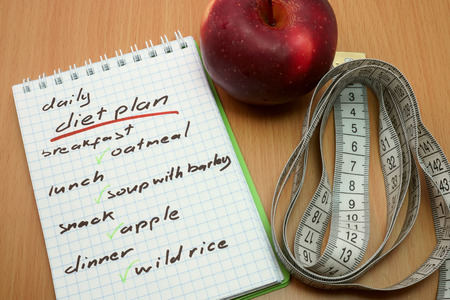 weight loss plan: Planning of a diet. Measuring tape, apple and a notepad with a  daily diet plan