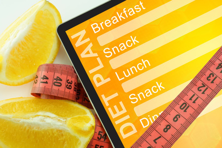Tablet with diet plan and measuring tape on white background photo