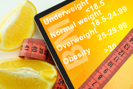 bmi: Tablet with words Body mass index BMI and measuring tape