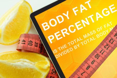 Tablet con el porcentaje de grasa corporal palabras y cinta métrica Foto de archivo